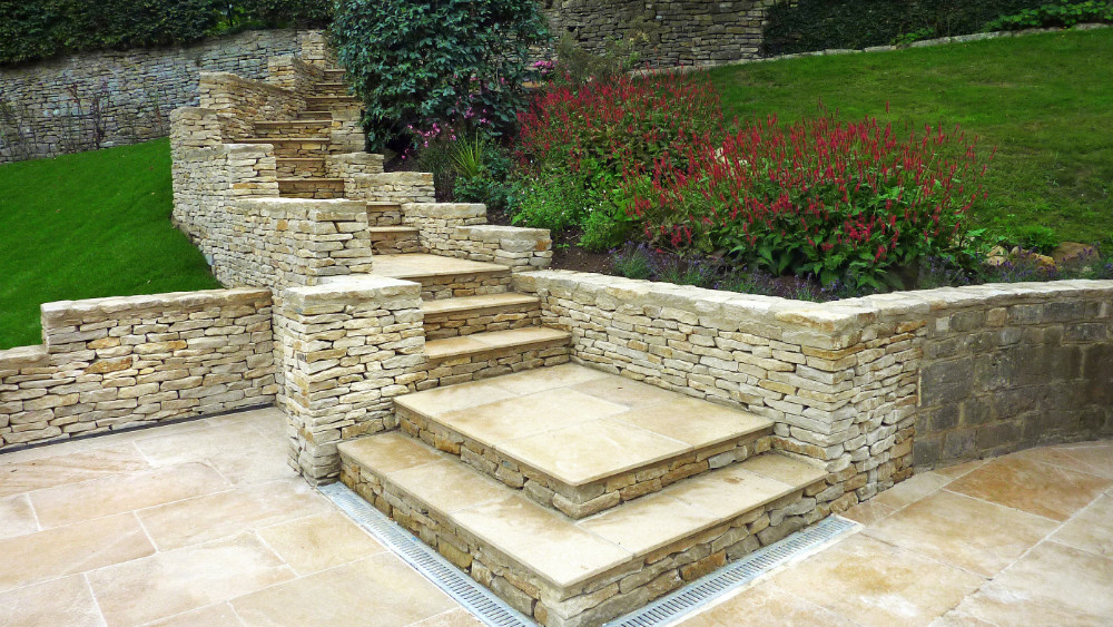 Cotswold drystone steps and walls, retaining walls to support flower beds. Grill at bottom of steps to allow water drainage