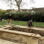 turf being laid, drystone walls being topped with stone slabs, new paving and planting