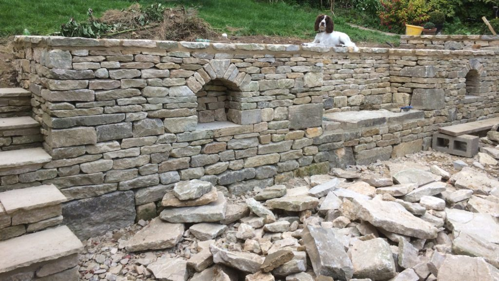 cotswold drystone retaining wall with seating and decorative alcoves incorporated