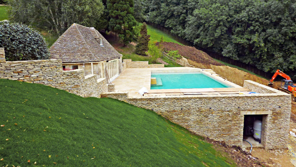 Cotswold stone wall and facing added to swimming pool surround