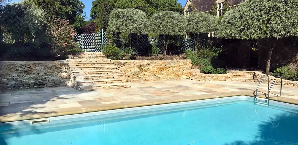 Beautiful Indian Sandstone surrounds the outdoor swimming pool with Cotswold stone steps leading up to lawn area. The flower beds are retained by Cotswold stone walls