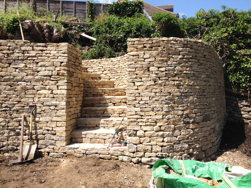 Cotswold drystone wall built with a curve to follow curved steps leading to the upper terrace