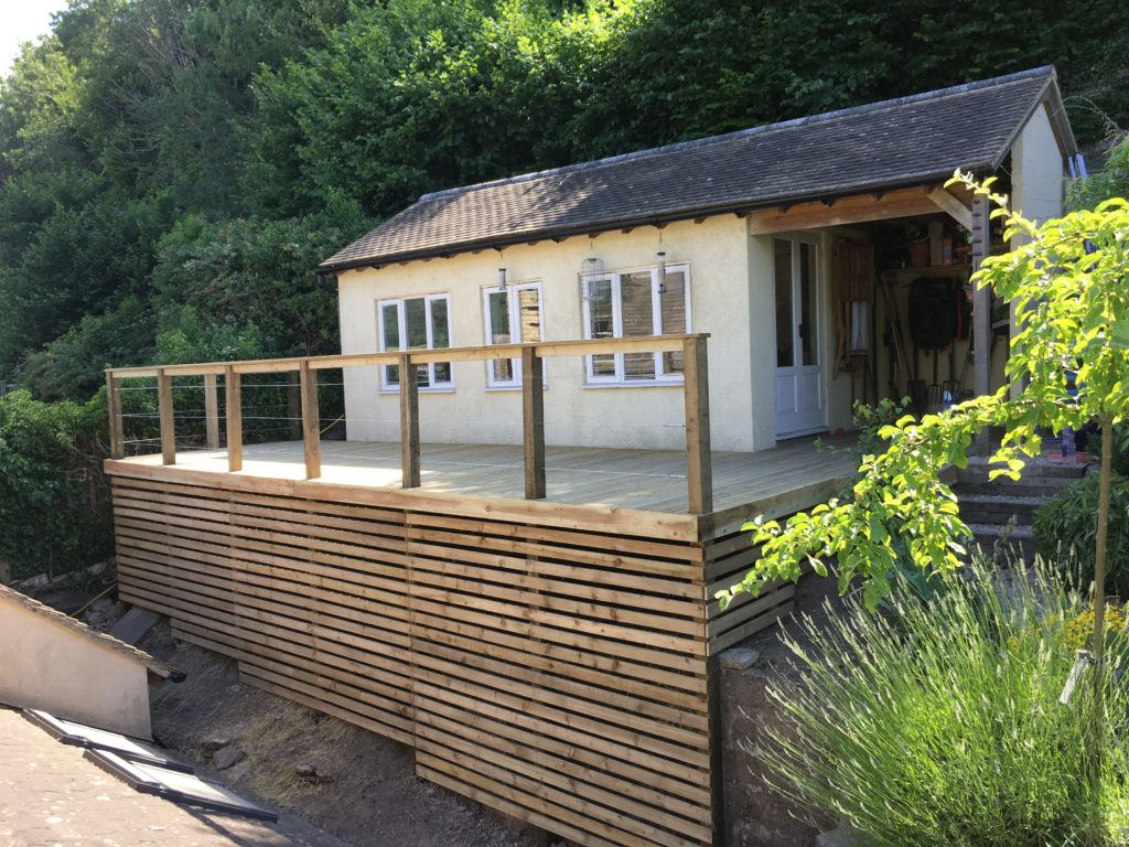 wooden decking built onto hill area in front of summer house, with wire balustrade