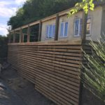 wooden decking built onto hill area in front of summer house